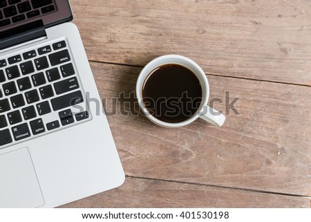 Top view Coffee cup and laptop on old wooden table