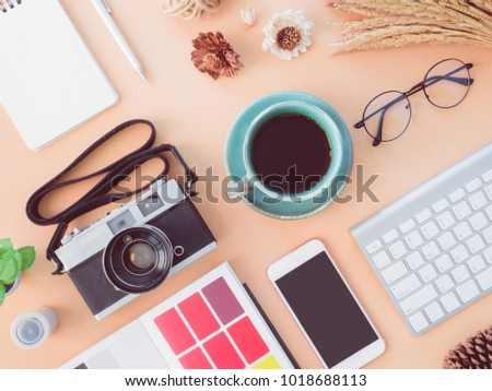 top view coffee shop and office table concept with coffee cup, retro camera, notebook, glasses, keyboard and smartphone on Pastel Color table background