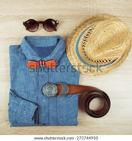 Top view collection of summer male clothing on the wooden background - stock photo