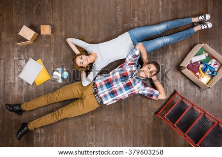 Top view creative photo of beautiful young couple on vintage brown wooden floor. Couple is ready for home renovation - stock photo