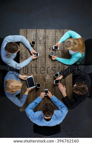 Top view creative photo of business people sitting at dark wooden vintage table. Business people having meeting. Concept for successful teamwork. There are electronic gadgets at table - stock photo