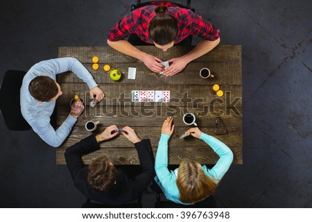 Top view creative photo of friends sitting at dark wooden vintage table. Friends having fun while playing cards - stock photo