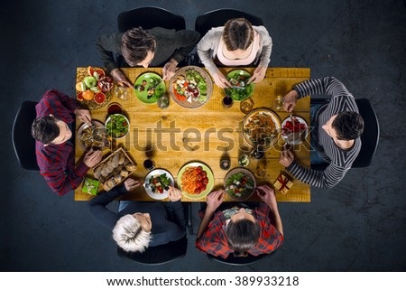 Top view creative photo of friends sitting at wooden vintage table. Friends of six having dinner. They with plates full of meal and glasses with drinks. There is free space in the middle of table - stock photo