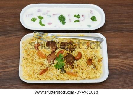 Top view Delicious North Indian food Hydrabadi chicken biriyani, vegetable Biriyani, Chicken pulao and yogurt starter. Fresh Vegetable salad. basmati rice, herbs, raitha. Ramadan Kareem,  Eid-Ul-Adha - stock photo