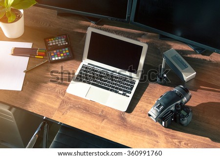 Top view Desktop shot of a modern Digital Medium Format Photo Camera with Laptop on stylish wooden desktop workplace / Background