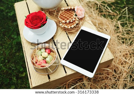 Top view digital tablet lying on wooden box with cookies, flowers and tea set at sunny day, touch pad wireless device. Weekend relax concept - stock photo