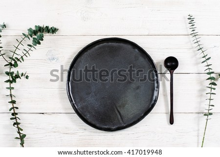 Top view empty black plate and cutlery on rustic wooden table. Ceramic black plate and spoon on white wooden background with free space. Flat lay of handmade black dish on white wooden table.  - stock photo