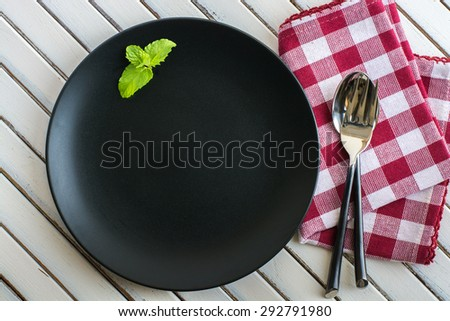 Top view empty black plate on rustic wooden table - stock photo