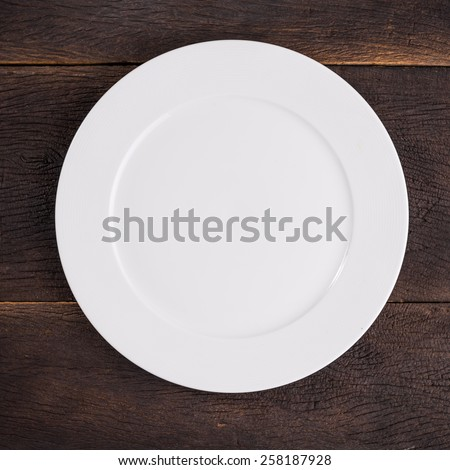 Top view empty white plate on dinner table. - stock photo