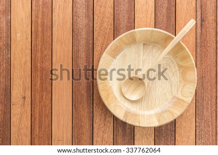 Top view empty wooden bowl and soup spoon on wooden table - stock photo