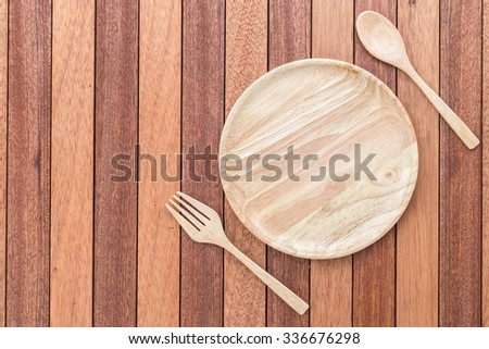 Top view empty wooden dish, fork and spoon on wooden table - stock photo