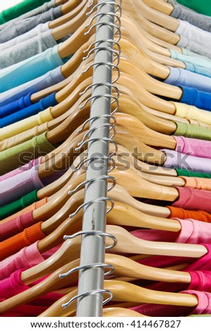 Top view  female clothes of different colors on wooden hangers