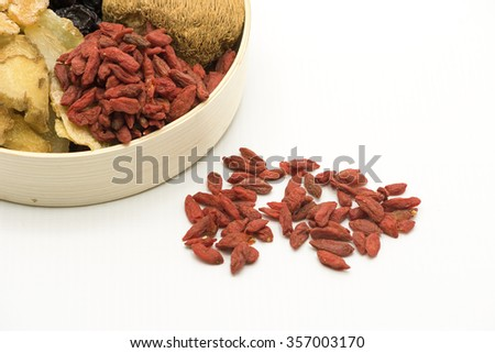 Top view focus on red goji berry and partial view of  a bamboo bowl with some assortment of Chinese herbal soup ingredients.  Isolated on white background. - stock photo