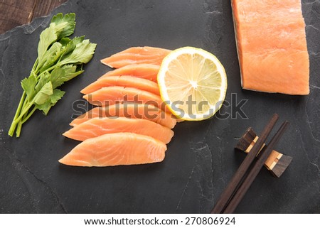 Top view fresh salmon with lemon on black background - stock photo