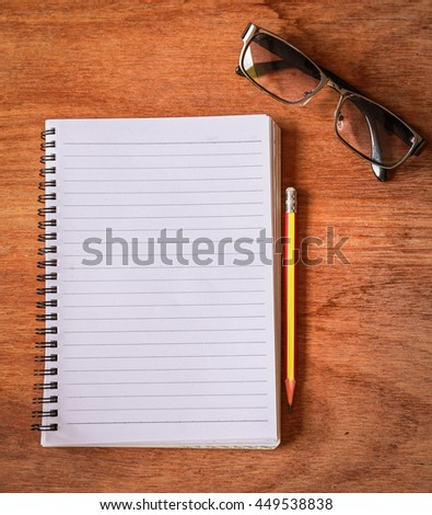 Top view from blank notepad workspace with pencil and glasses on wooden table background. Copy space for text - stock photo