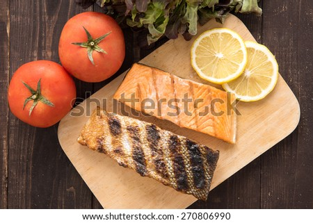 Top view grilled salmon on cutting board on wooden background - stock photo