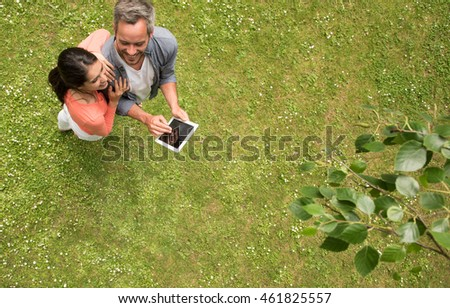 Top view. Handsome couple using a digital tablet, standing barefoot in the grass. The man has grey hair