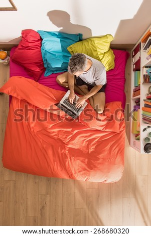 top view, handsome man sitting on bed using a laptop by a sunny morning, the bedding has bright colors. The flat is luminous and modern - stock photo