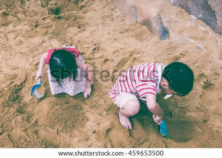 Top view. Happy brother and sister playing with sand. Adorable asian children have fun digging in the sand on a summer day. Vintage tone. Outdoors. - stock photo