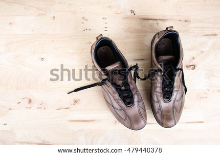 Top view high angle shot pair of brown leather shoes  on  wooden floor White brick wall background