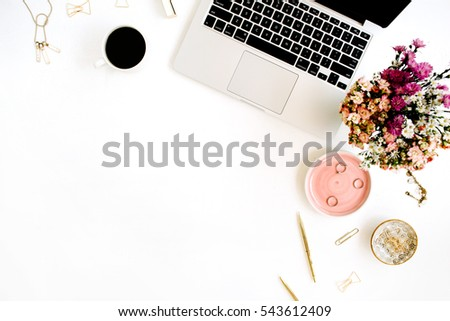 Top view home office desk. Workspace with laptop, wildflowers bouquet, coffee cup, golden pen, clips and accessories. Flat lay. Woman entrepreneur background with laptop