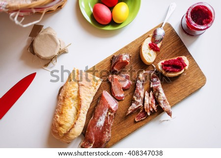 Top view horizontal image of various meats on serving board. Ham, pork, beef, easter eggs and homemade bread with beetroot-horseradish spread. Preparing for dinner to celebrate Easter. Selective focus - stock photo