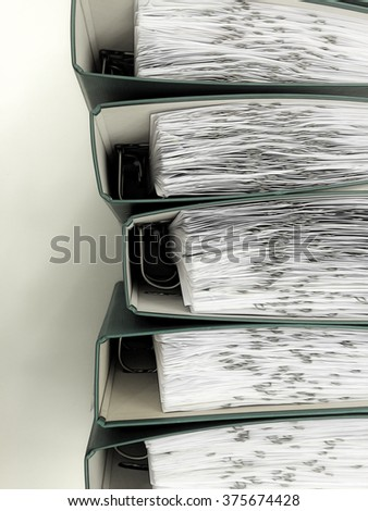 Top view illustration of a row of green closed office ring binders filled with archived documents - stock photo