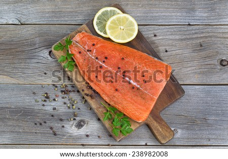 Top view image of a fresh salmon fillet with herbs, spices and lemon slices on rustic wood ready to be cooked.  - stock photo