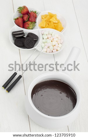 Top view image of a tempting desserts together with the melted chocolate bowl and fondue stick against white background - stock photo