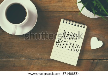 top view image of blank notebook with phrase: happy weekend, next to cup of coffee and little wooden heart. vintage filtered and toned  - stock photo