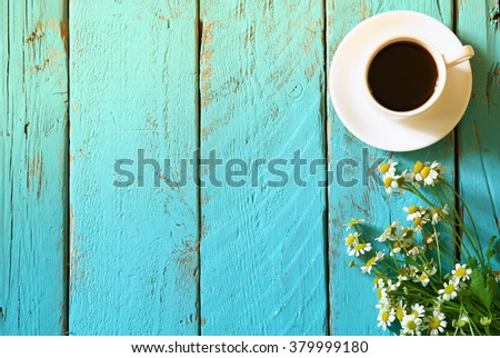 top view image of daisy flowers next to cup of coffee on blue wooden table. vintage filtered  - stock photo