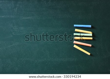 top view image of green chalkboard and collection of many chalks. room for text  - stock photo