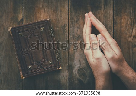 top view image of mans hands folded in prayer next to prayer book. concept for religion, spirituality and faith. vintage filtered and toned  - stock photo
