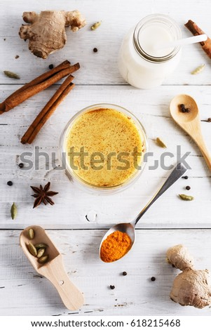 Top view image of turmeric latte, spices and bottle of milk over white wooden table