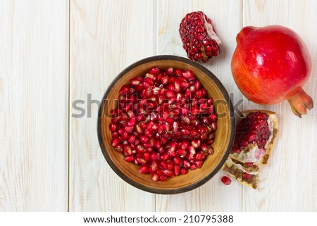 Top view, Juicy pomegranates on wood background  - stock photo