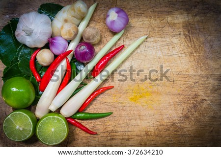 Top view. Kaffir lime leaf, lemon, lemongrass, galangal, chili, onions and Straw mushroom herb and spicy ingredients Thai food on chopping block on wood background. Low key and vignette picture style. - stock photo