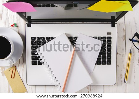 Top view ,Laptop (notebook) with cup of coffee and notepad,book with pen on wood table.Desk Office - stock photo
