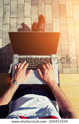 Top view male hands using notebook outdoors in urban setting while typing on keyboard, businessman freelancer working on computer while sitting on city park bench, tourist working on laptop, flare sun - stock photo
