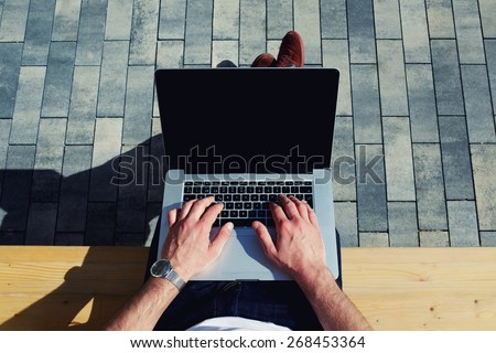 Top view male hands using notebook outdoors in urban setting while typing on keyboard, businessman freelancer working on computer while sitting on city park bench, tourist working on laptop, filter - stock photo