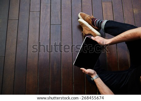 Top view male student using touchpad while sitting on wooden floor, modern successful businessman working on his digital tablet with big copy space,hipster man's hands browsing with touchscreen device - stock photo