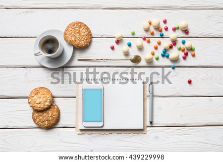Top view mock up of white smart phone on a cafe desktop among cookies with coffee cup. Clipping path included.