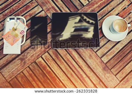 Top view mock-up with touch screen digital tablet, smart phone, bill check with money and cup of coffee on the wooden desk, gadgets with empty blank screen, work break of businessman, flare sun light - stock photo