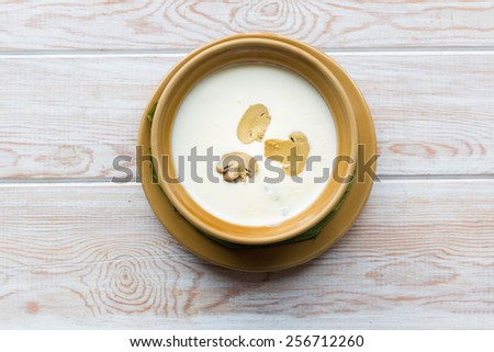 Top view, Mushroom soup in pot, on wooden background  - stock photo