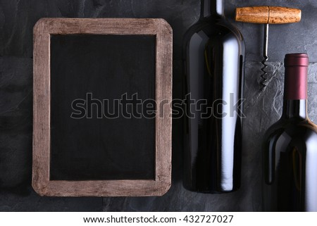 Top view of a blank chalk board for a wine list or menu with two bottles and old cork screw. Side light on a slate table.