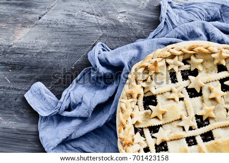 Top view of a blueberry pie with lattice and stars crust with grey napkin over an industrial artistic wooden background.