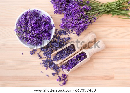Top view of a bowl and wooden spoons with dried and fresh lavender flowers and a bouquet of lavender on a wooden background