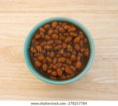 Top view of a bowl filled with country style baked beans on a wood table top. - stock photo