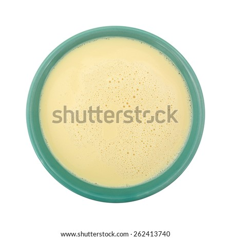 Top view of a bowl filled with evaporated milk on a white background. - stock photo