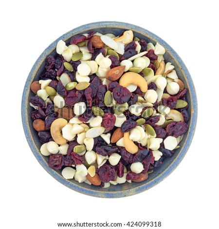Top view of a bowl full of an assortment of nuts and dried cranberries trail mix isolated on a white background.