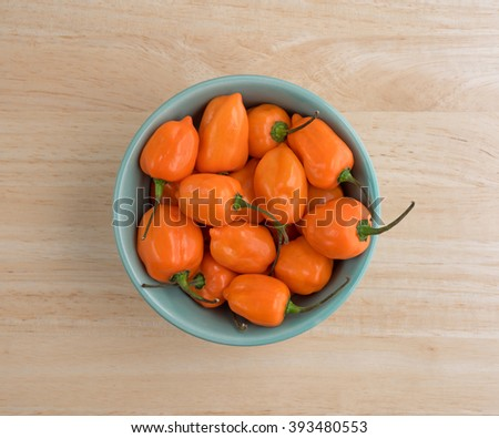 Top view of a bowl of orange habanero peppers on a wood kitchen counter top.